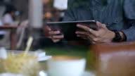 man using Digital Tablet at Indoor Cafe.