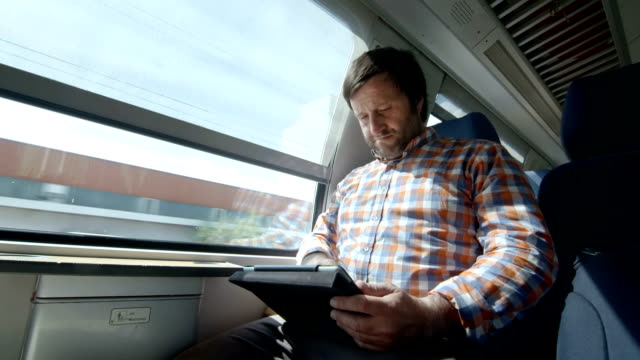 HD: Man Using Digital Tablet On A Train