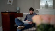 Man using digital tablet while sitting on armchair