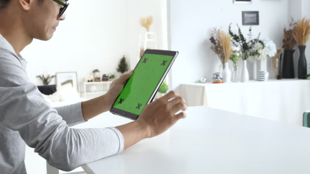 Man using digital tablet with a green screen at home, Vertical