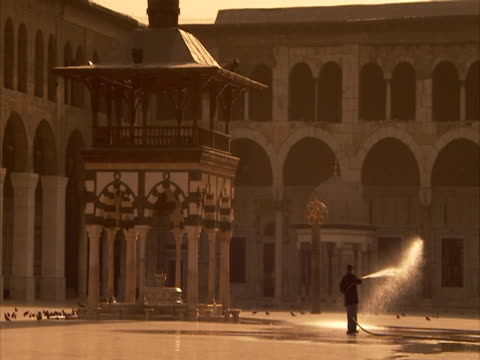 Man using hose in Umayyad mosque courtyard, pigeons fly off from ground, Syria (sound available)