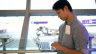 Man using laptop computer in airport terminal