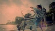 Man using laptop on dock on shore of lake / pausing to think / resuming work