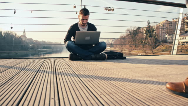 WS Man Using Laptop While Sitting On Bridge