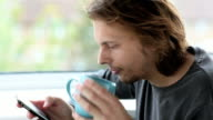 Man using mobile phone and drinking coffee
