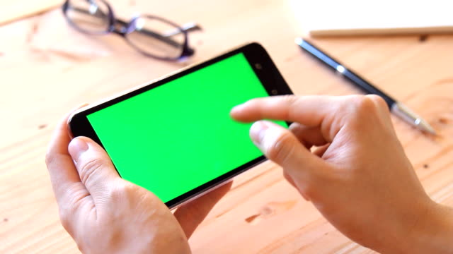 man using mobile phone with green screen on wooden office table - multiple gestures