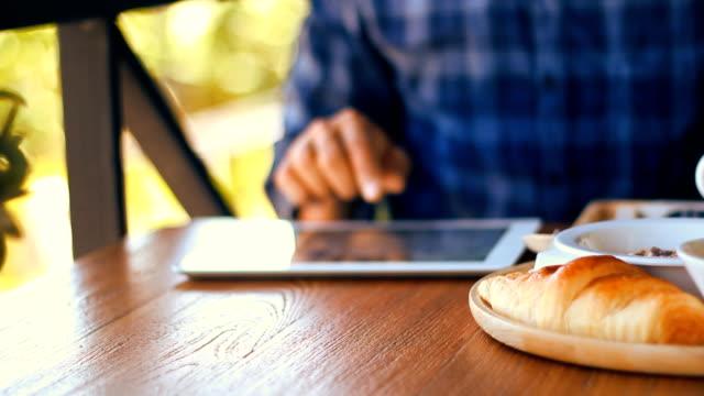 Uomo utilizzando pad e avendo la colazione nella caffetteria