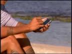 Man using PDA at beach