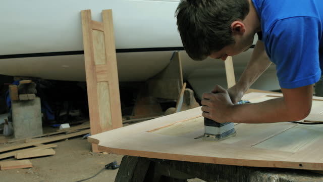 CU Man using power tool to sand woodwork in workshop