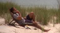 MS Man using smart phone on lounge chair on beach, Eastville, Virginia, USA