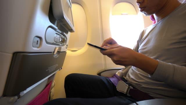 Man using smart phone on the plane
