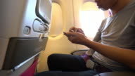 Man using smart phone on the plane
