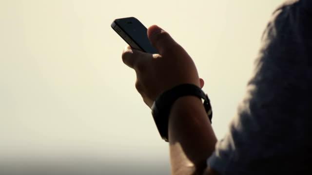 Man using smartphone and look around.