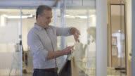 Man met behulp van smartphone en het nemen van een foto van een weergave in een winkelcentrum