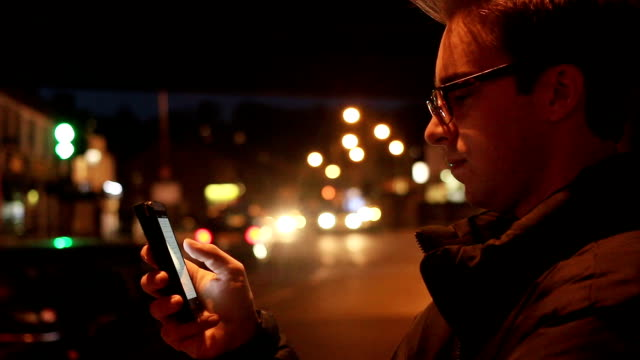 Man using smartphone, night.
