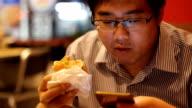 Uomo utilizzando uno smartphone mentre mangia hamburger