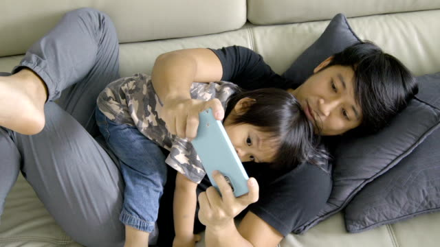 Man using smartphone with baby laying on chest.