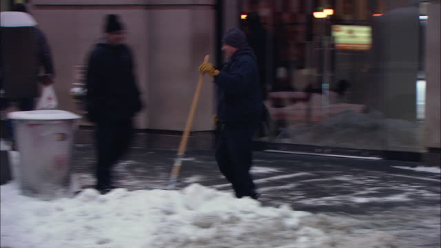 WS PAN Man using snow blower to clear sidewalk in front of business / New York, New York, United States