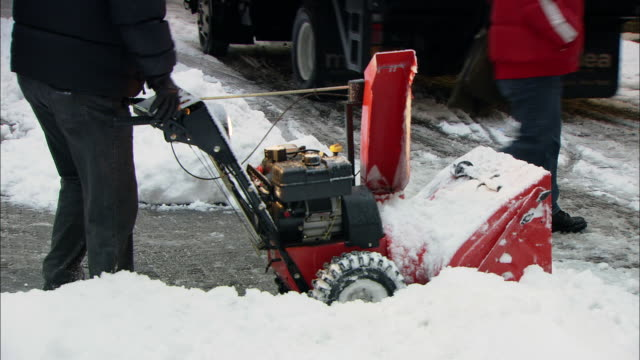 MS ZO PAN Man using snow blower to clear snow in Wall St. area / New York, New York, United States