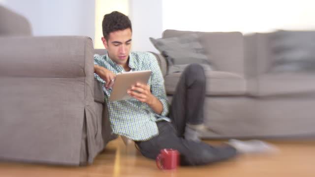 man using tablet on floor