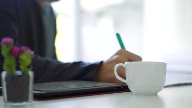 Man Using Tablet PC and Drinking Coffee