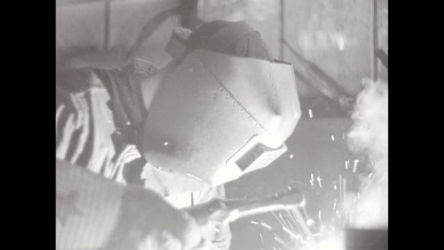 CU Man using welding torch and welder's visor while welding in workshop / United States