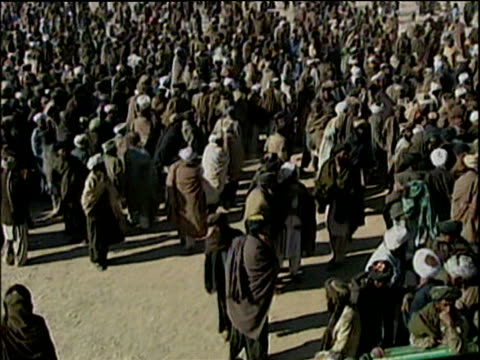 Man using whip to try to control crowds in refugee camp; Afghanistan Refugee Crisis 2001