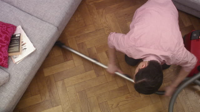 A man vacuuming under a couch Sweden.