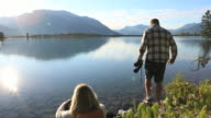 Man views mtn scene through binoculars, while woman relaxes