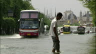 A man wades across a floodwater covered street as a metro bus approaches