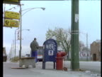 Man waits at bus stop beside graffiti covered post box and red fire hydrant flags bus gets on bus exits shot.
