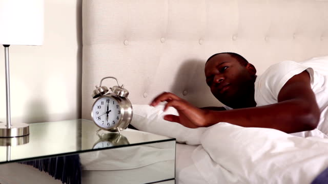Man waking up and turning off his alarm clock