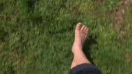 man walking about meadow with bare feets, close of feets, from above