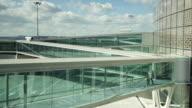 WS Man walking along glass walkway away from airport building / Toulouse, Haute-Garonne, France