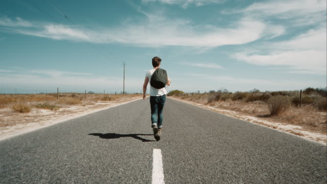 Man lopen langs de weg