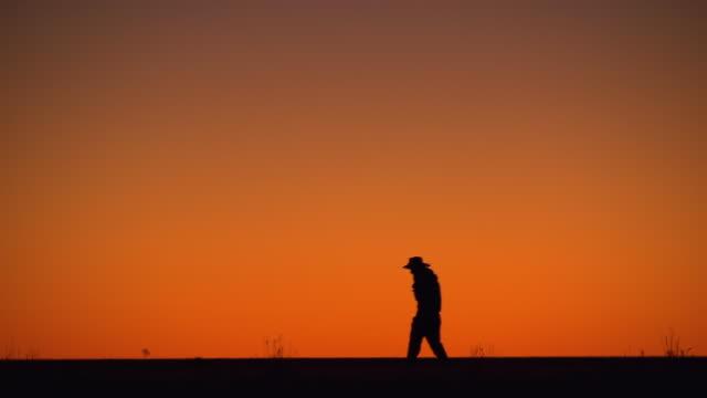 WS Man walking at sunsetting / Boulia, Queensland, Australia