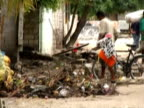 MS man walking bike across village side street with rubble on ground caused by tsunami, Maldives