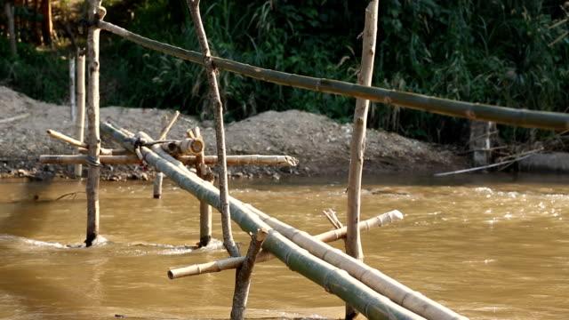 Man walking cross river on bamboo bridge