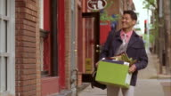 MS Man walking down street with belongings in box, being greeted at new job by associate, Kansas City, Missouri, USA
