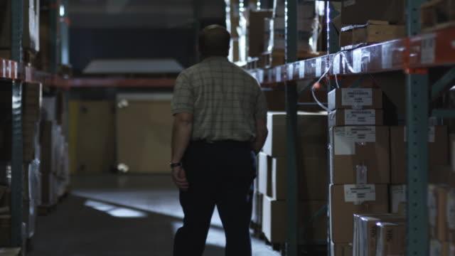 WS Man walking down warehouse corridor, Dallas, Texas, USA