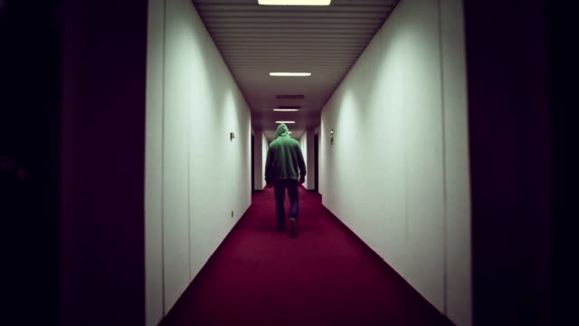 Man walking in a creepy hotel corridor