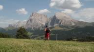 Man walking in Dolomites Sasso Lungo and Piatto on background
