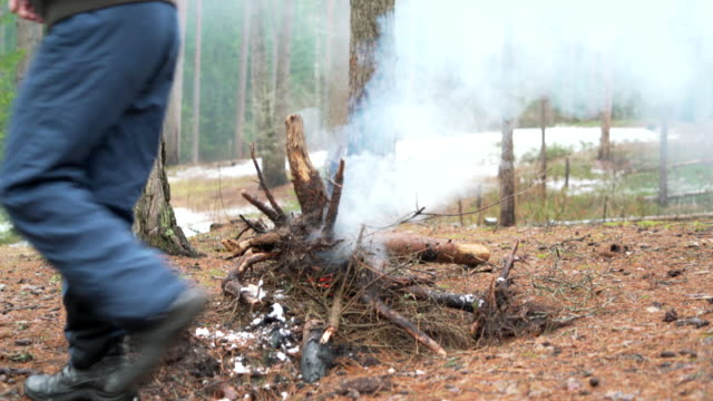 Man walking in front of the bonfire in the winter forest.