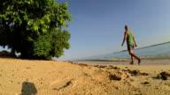 Man walking in the beach towards a tree