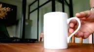 man zu Fuß ins Wohnzimmer und Abholung Kaffeetasse - indoor-Szene