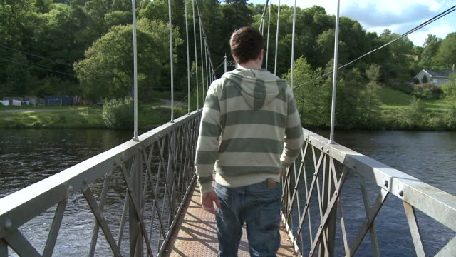 MS Man walking on bridge / Charlestown of Aberlour, Speyside, Scotland