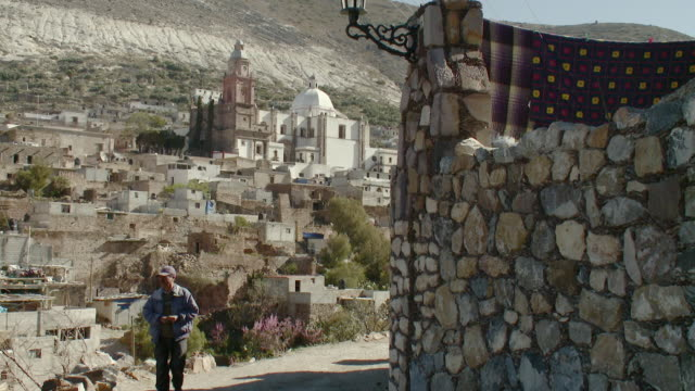 WS Man walking on cobblestone street with town in background / Real de Catorce, San Luis Potosi, Mexico
