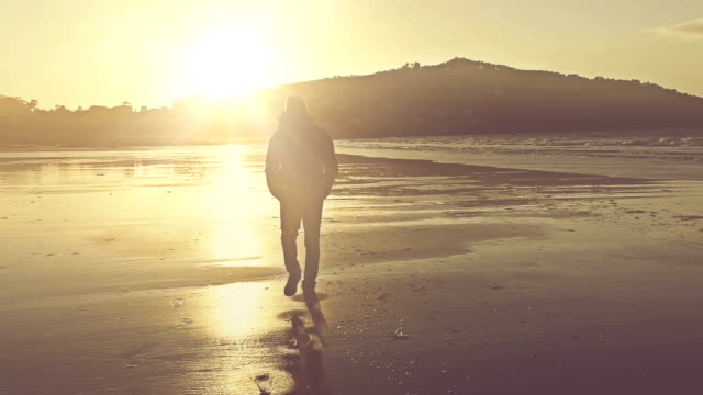 Man walking on the shore at sunset