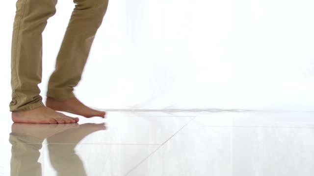 Man walking on tiled white floor