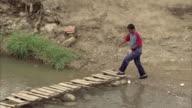 WS PAN HA ZO Man walking over stream on footbridge in rural area / Tachira, Venezuela